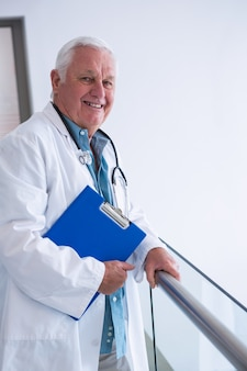 Doctor holding clipboard in the passageway at hospital