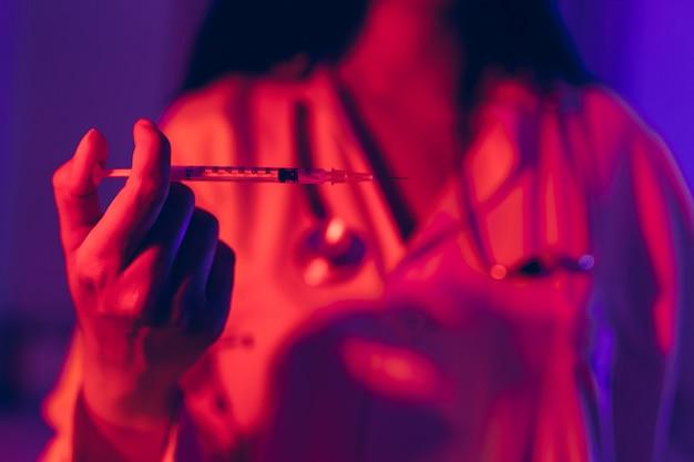 Доктор держа коронавирусную вакцину в шприце используя для предотвращения инфекции в ультрафиолетовом неоновом свете.