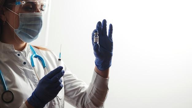 Врач, держащий вакцину против коронавируса, готовится к клиническим испытаниям на людях. концепция вакцины covid-19.