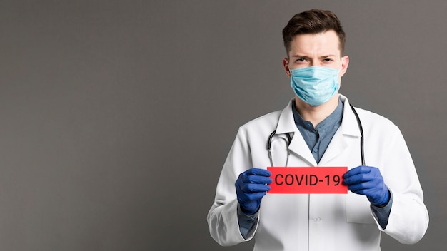 Doctor holding covid-19 card copy space
