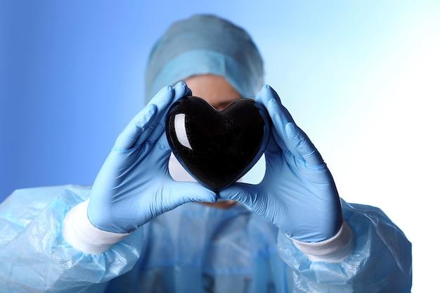 Доктор держит декоративное сердце на синем