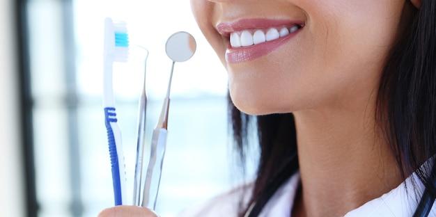 Врач, держащий инструменты стоматолога