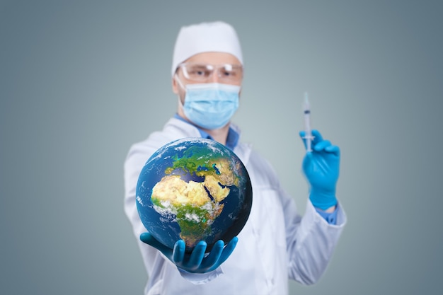 손과 의료 주사기에 지구 지구를 들고 의사
