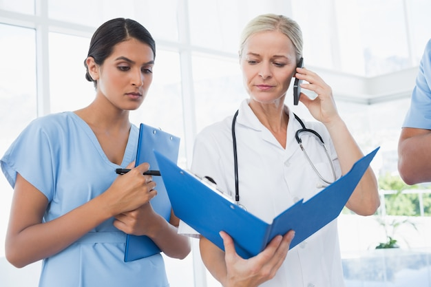 Doctor holding folder and having phone call
