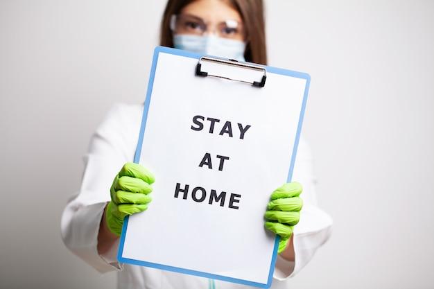Доктор держит форму, призывающую оставаться дома во время карантина