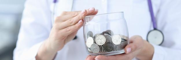 동전 근접 촬영으로 유리 항아리를 들고 의사 지불 의학 개념