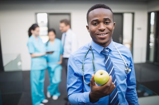 Doctor holding green apple in hospital corridor
