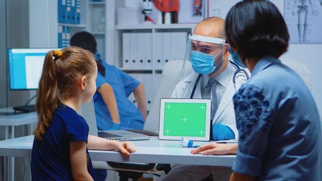 机の上に座っている診療所でグリーンスクリーンタブレットを保持している医師。クロマキーノートブック分離モックアップ交換画面を持つ医療専門家。簡単キーイング医学医療関連のテーマ。