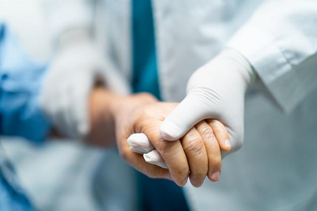 検疫室covid-19コロナウイルスでアジアの年配の女性に感染した患者の手を握って医師。