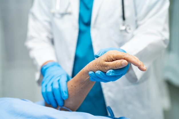 Doctor holding hands asian senior woman patient infected with covid-19 coronavirus.