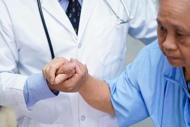 医師の愛を持つアジアの年配の女性患者の手を繋いでいます。