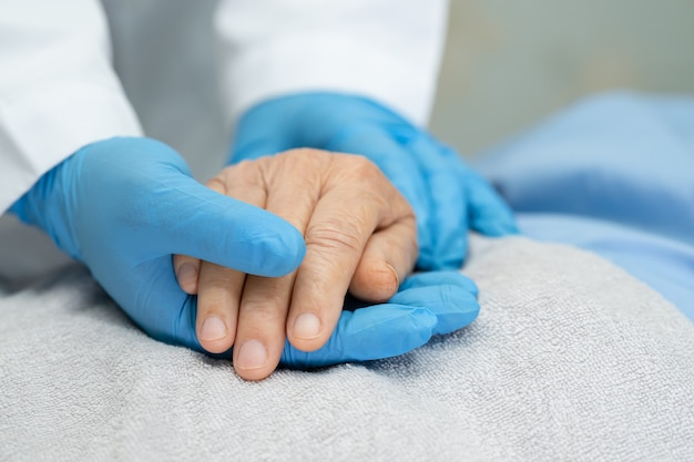 Doctor holding hands asian senior woman patient with love.