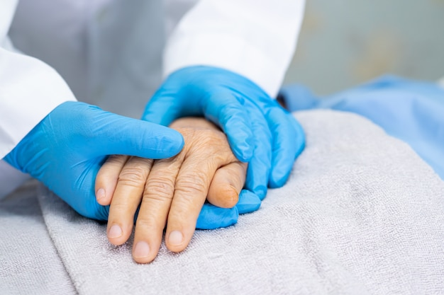 Doctor holding hands asian senior woman with love and care