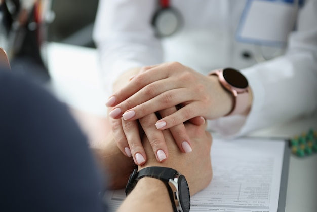 Doctor holding hands of patient in office closeup. fatal diagnosis concept