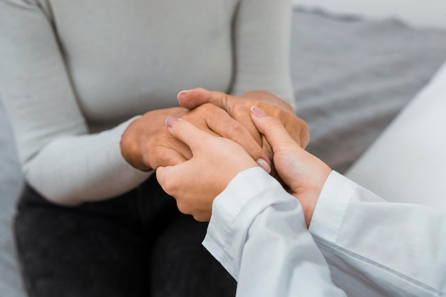 Medico che tiene le mani con il paziente