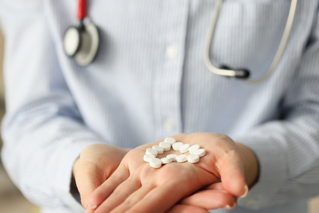 Doctor holding heart shaped pills in hand closeup