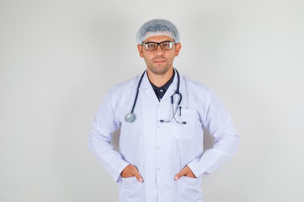 Medico che tiene le mani nelle tasche in camice bianco e cappello e che sembra positivo,