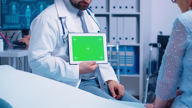 現代の民間病院または診療所で高齢患者の前に水平グリーンスクリーンクロマタブレットを持っている医師。アプリ、テキスト、ビデオ、またはその他のデジタル資産用の準備ができたクロマモックアップ