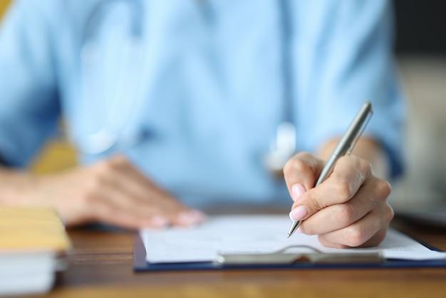クリップボードのクローズアップで銀のペンの書き込みを手に持っている医師