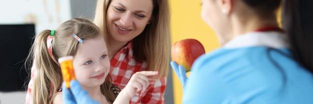小さな女の子と母親の前で薬とリンゴの瓶を保持している医師