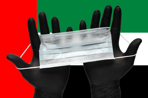 아랍에미리트(uae) 아랍에미리트(uae) 국기 배경에 검은 장갑 두 손으로 얼굴을 위한 의료 마스크를 들고 있는 의사. 개념 검역, 전염병 보험 코로나바이러스, 발병 공기 매개 질병.