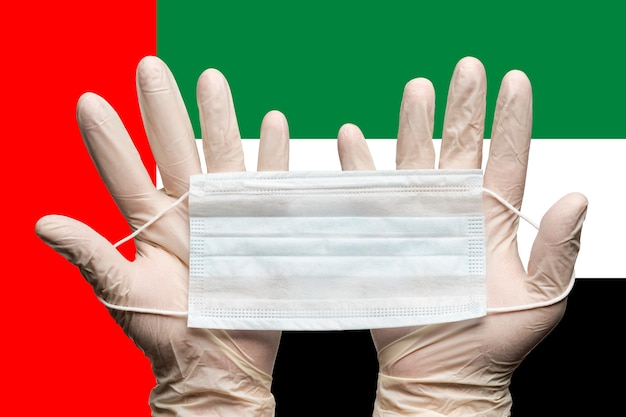 Doctor holding medical mask in two hands in gloves on background flag of united arab emirates uae