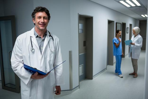 病院の廊下で医療レポートを保持している医師