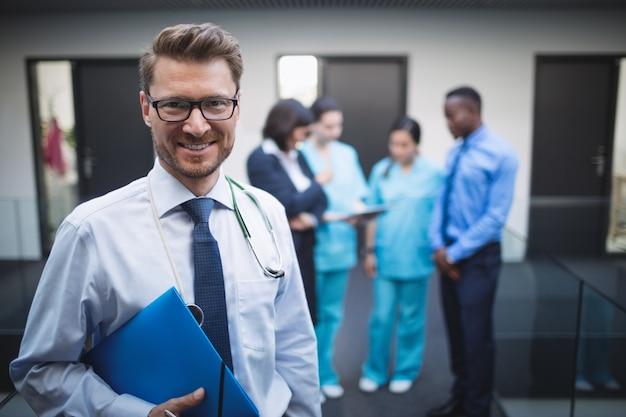 病院の廊下で医療報告書を保持している医師