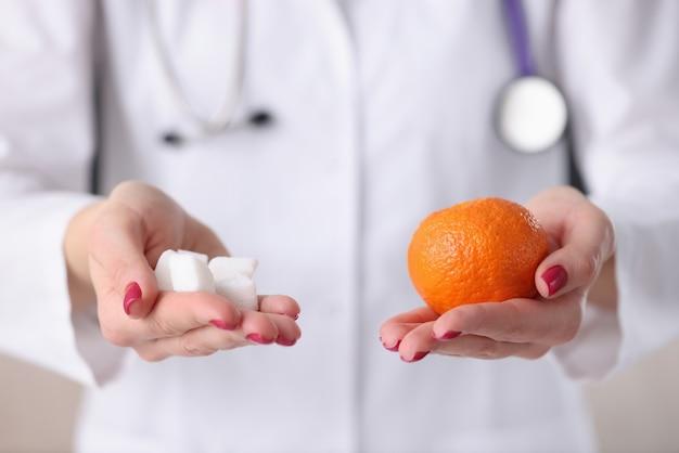 Доктор, держа в его руках кубики апельсина и сахара. концепция профилактики диабета