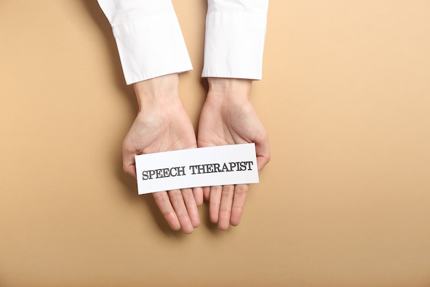 Doctor holding paper with text speech therapist on color surface
