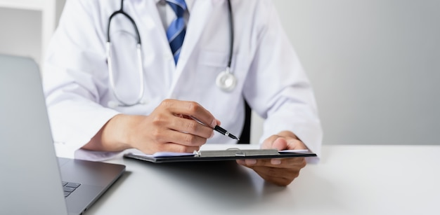 Doctor holding the patient report file to assess symptoms on the desk.