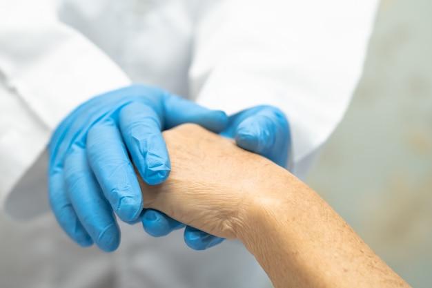 医者は患者の手を握って