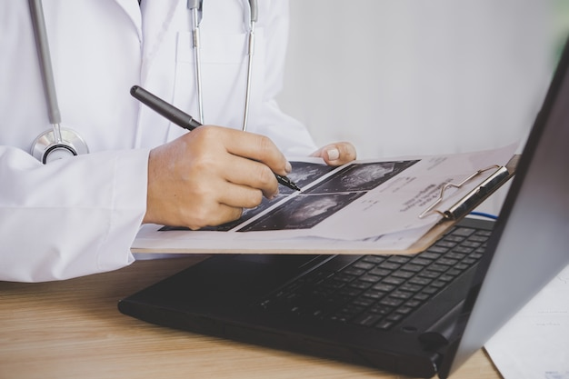 Doctor holding pen in hand analyzing x-ray medical picture while working on  laptop