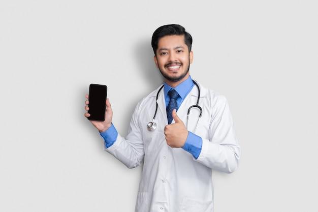 孤立した親指を上に表示している電話を保持している医師。自宅でパキスタンの男性医師技術医学。電話クリア画面。