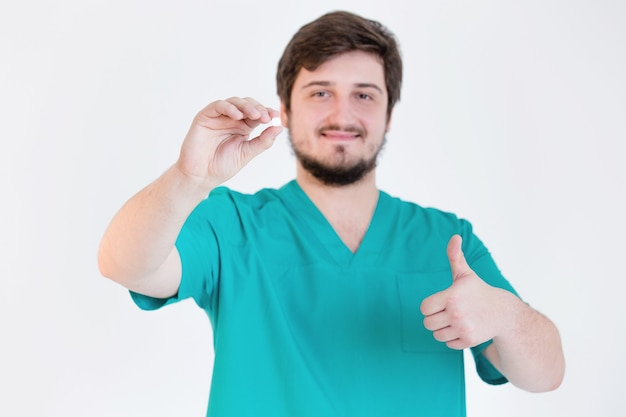 Doctor holding pill on white wall
