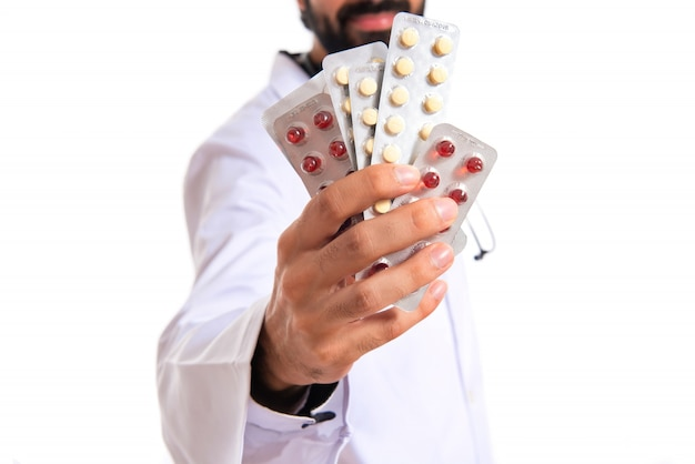 Doctor holding pills over white background