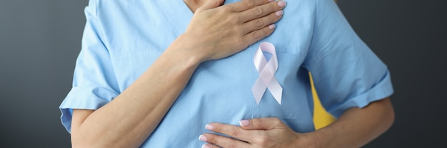 Doctor holding pink ribbon in hand near chest in clinic close-up