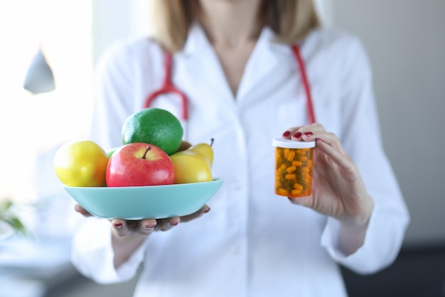 Doctor holding plate of fruit and jar of medicine closeup. taking vitamins concept
