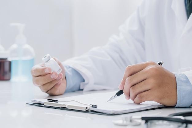Доктор держит бутылку с рецептом и писать рецепт в специальной форме в офисной комнате. концепция здравоохранения, вакцины, медицины и аптеки.