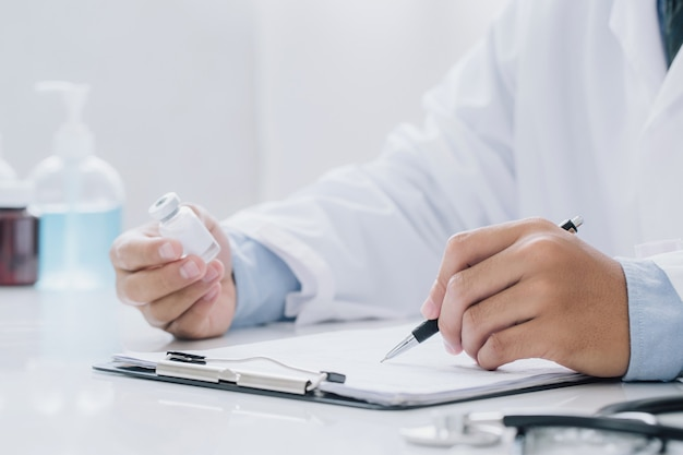 Doctor holding prescription bottle and writing prescription on special form at office room. healthcare, vaccine,medical and pharmacy concept.