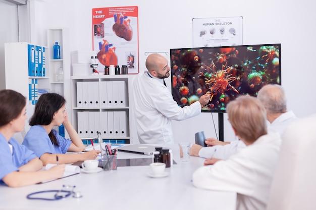 의사가 omf 의료 팀 앞에서 코로안바이러스 증상에 대한 프레젠테이션을 들고 있습니다. 위험한 바이러스로 인한 세계적 대유행에 대해 동료들과 논의하는 전문 의사,