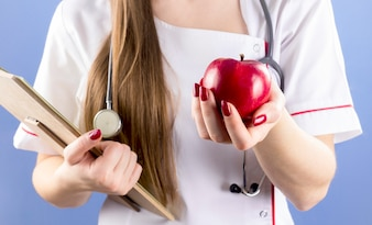 Doctor holding red apple in hand