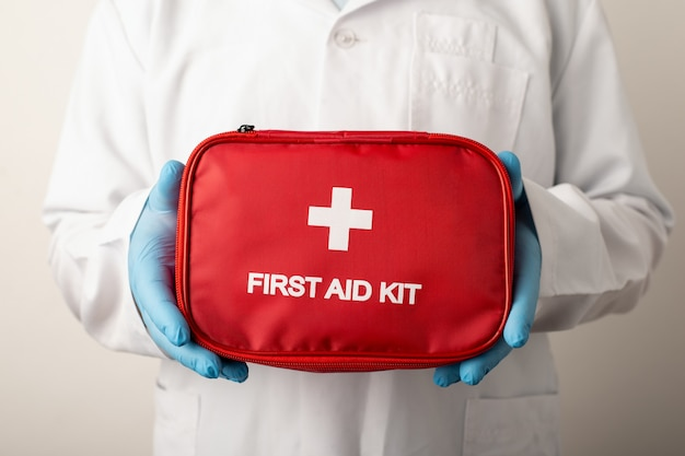 Doctor holding red box with inscription first aid kit. concept of healthcare system, treatment