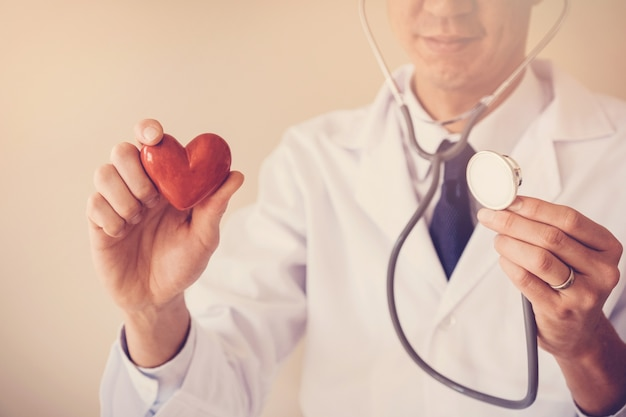 Doctor holding red heart, heart health insurance concept
