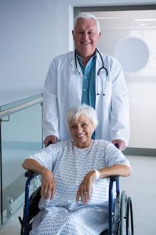 病院の通路で車椅子のシニア患者を保持している医師
