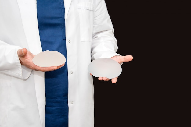 Doctor holding silicone implant for breast augmentation, space for text. plastic surgeon hands holding silicon breast implants. cosmetic surgery