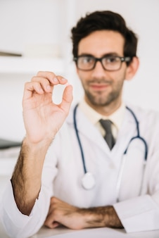 Doctor holding small pill in his hand