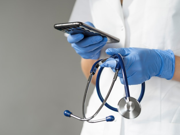 Doctor holding smartphone and stethoscope