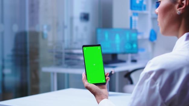 클리닉 캐비닛에 복사 공간이 있는 스마트폰을 들고 있는 의사와 유리문을 여는 간호사. 모형이 있는 스마트폰을 사용하여 병원 캐비닛의 의료 전문가입니다.