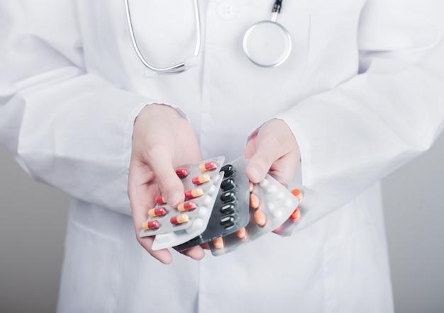 Доктор, держащий стопку различных таблеток, антибиотиков с витаминами и таблетками для лечения вирусов на серой стене больницы.